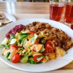 jauhelihakaalilaatikkoa puolukkasurvoksella ja salaatin, leipien ja mehun kera